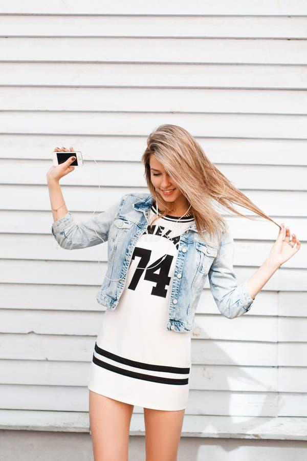Jeune femme avec du charme heureuse dans une robe blanche sportive dans une veste élégante de denim posant sur la rue près d'un m image stock