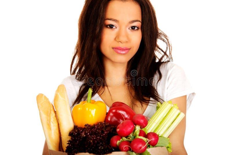 Jeune femme avec l'épicerie et les légumes images stock