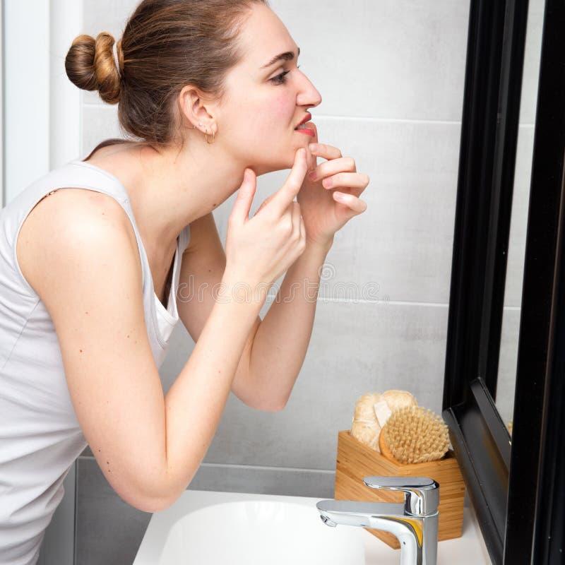 Jeune femme avec l'acné serrant ses taches avec le miroir de salle de bains photos stock