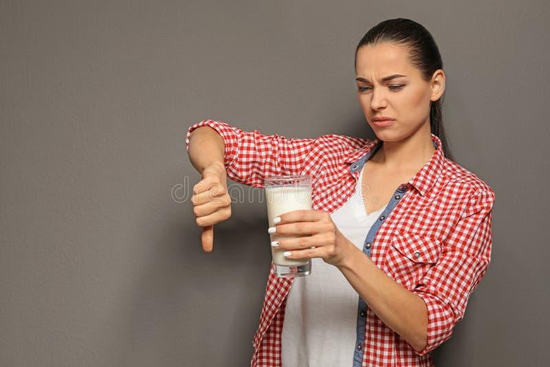 Jeune femme avec l'allergie de laiterie tenant le verre de lait images stock