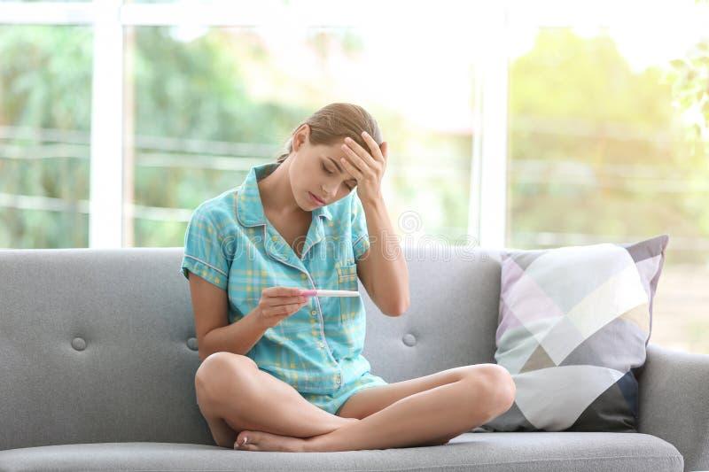 Jeune femme avec l'essai de grossesse à la maison images libres de droits