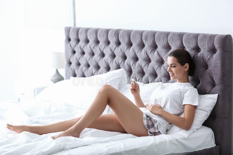 Jeune femme avec l'essai de grossesse dans la chambre à coucher image stock
