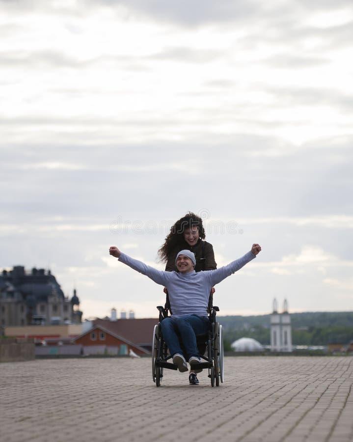 Jeune femme avec l'homme handicapé heureux dans le fauteuil roulant ayant l'amusement dehors photographie stock libre de droits