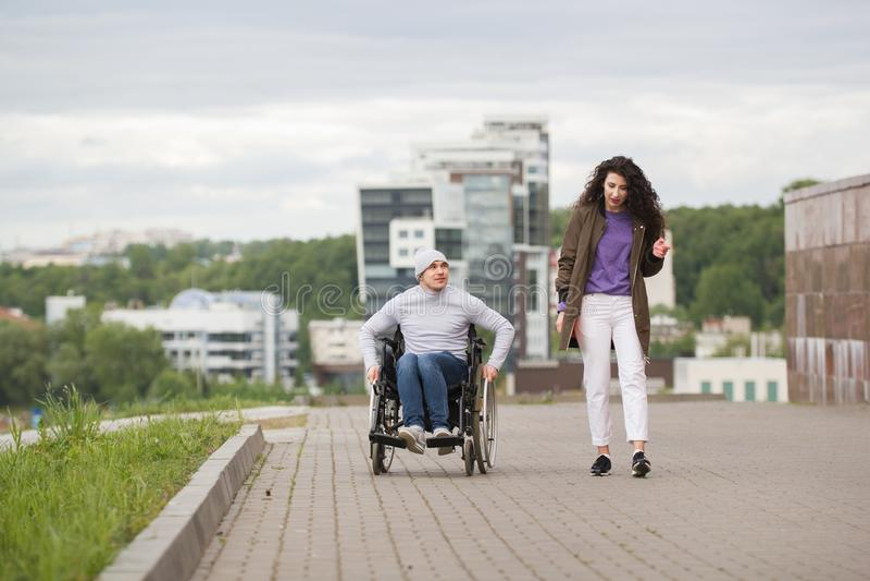 Jeune femme avec l'homme handicapé heureux dans le fauteuil roulant ayant l'amusement dehors photos libres de droits