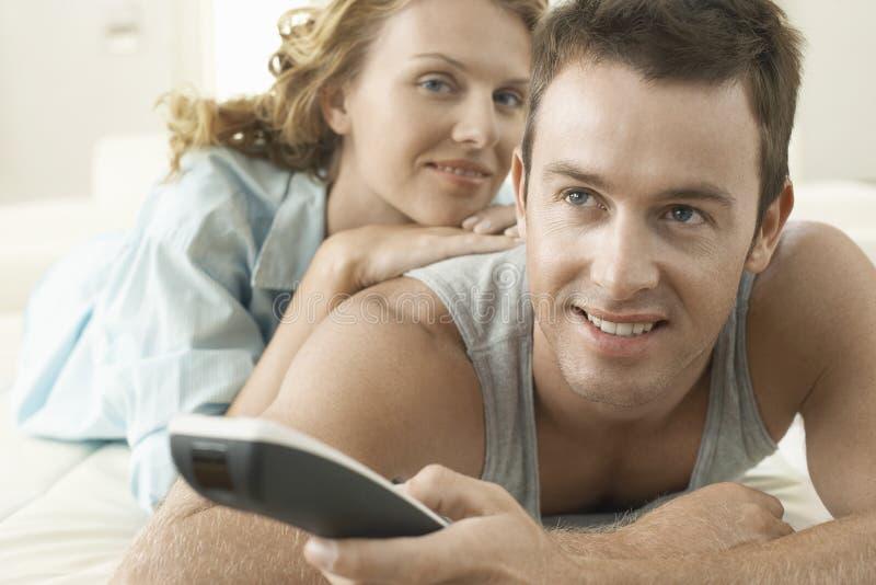 Jeune femme avec l'homme jugeant à télécommande image stock