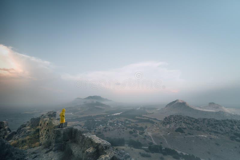 Jeune femme avec l'imperméable se tenant sur le bord du ` s de falaise et regardant à un ciel image libre de droits