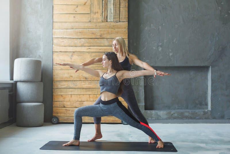 Jeune femme avec l'instructeur de yoga dans le centre de fitness, pose de guerrier photographie stock libre de droits