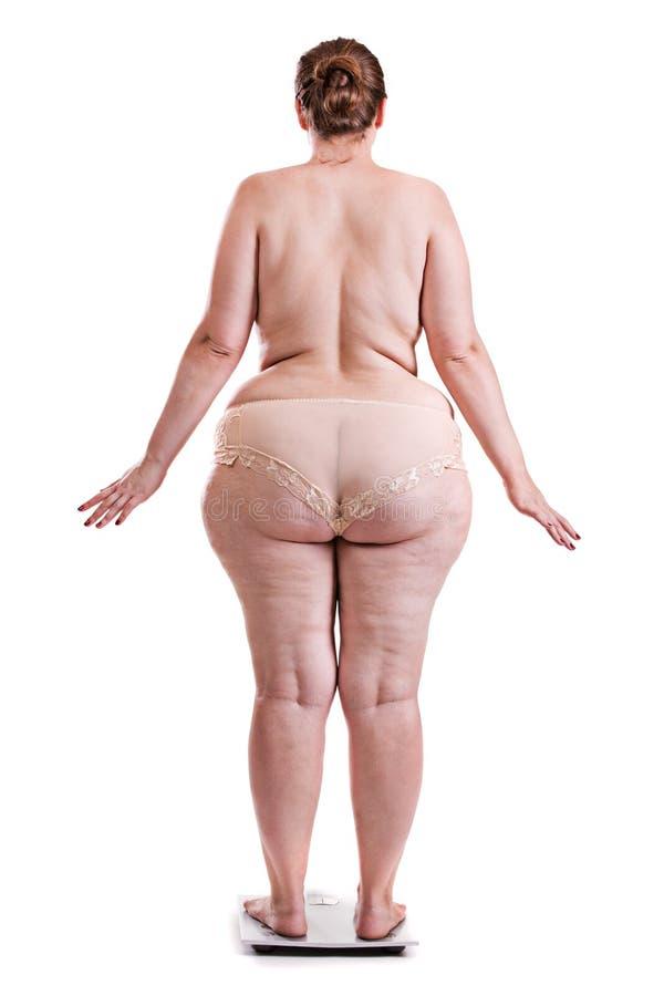 Jeune femme avec l'obésité sur les échelles image stock