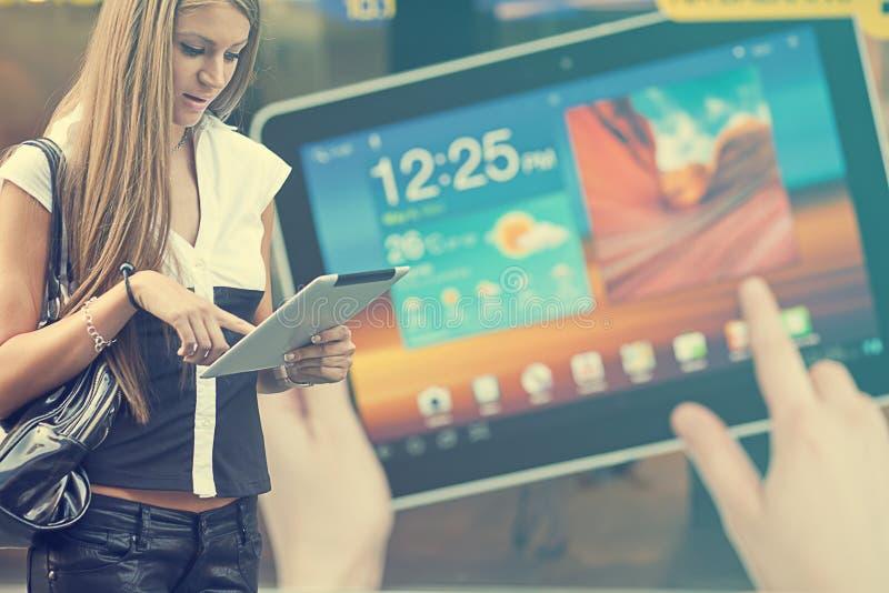 Jeune femme avec l'ordinateur de tablette marchant sur la rue photos libres de droits