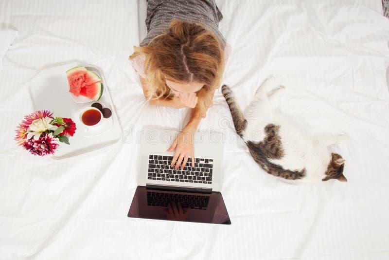 Jeune femme avec l'ordinateur portable dans le lit photo stock