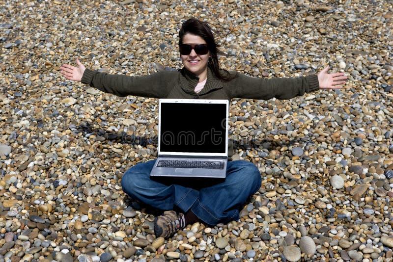Jeune femme avec l'ordinateur portable en plage photographie stock
