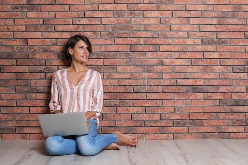 Jeune femme avec l'ordinateur portable moderne se reposant sur le plancher photo libre de droits