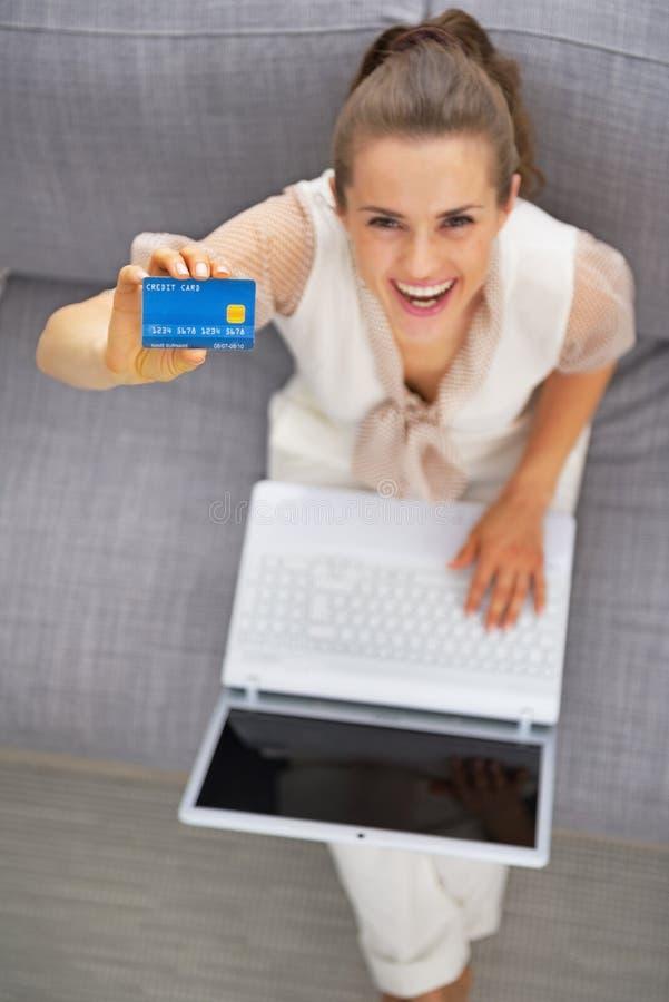 Jeune femme avec l'ordinateur portable montrant la carte de crédit photo libre de droits