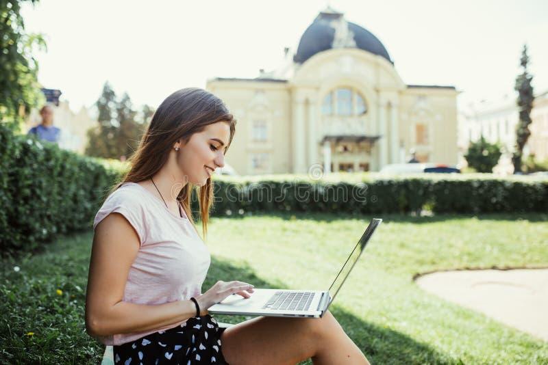 Jeune femme avec l'ordinateur portable se reposant sur l'herbe, image avec l'endroit pour le texte images stock
