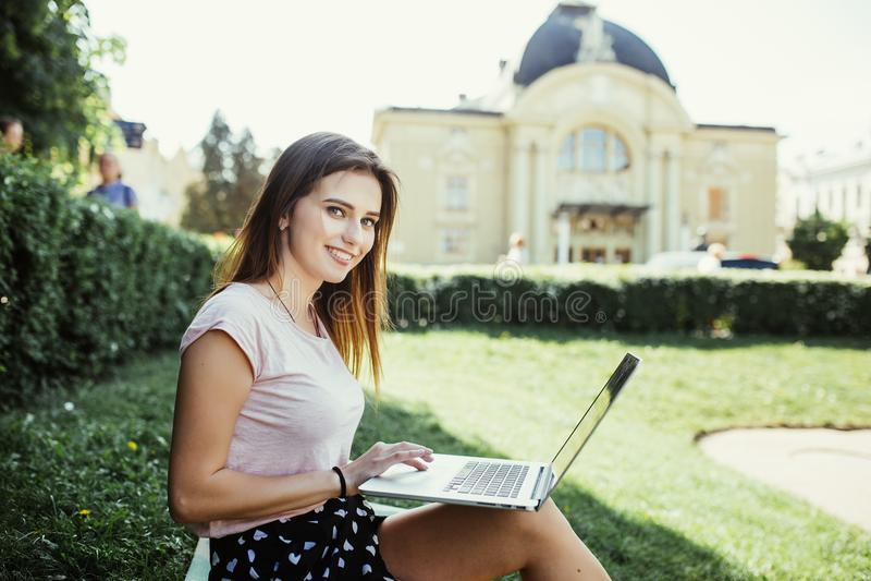 Jeune femme avec l'ordinateur portable se reposant sur l'herbe verte dans la rue de ville photographie stock libre de droits