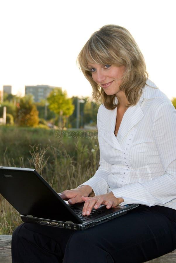 Jeune femme avec l'ordinateur portatif image libre de droits