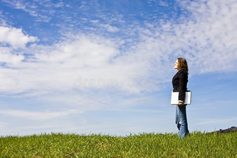 Jeune femme avec l'ordinateur portatif dans le pré image libre de droits