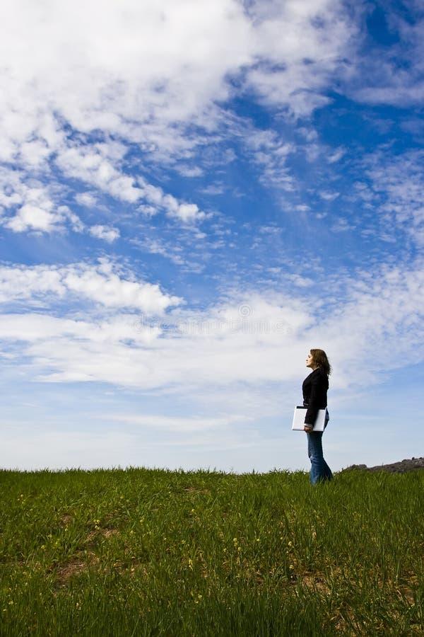 Jeune femme avec l'ordinateur portatif dans le pré image stock