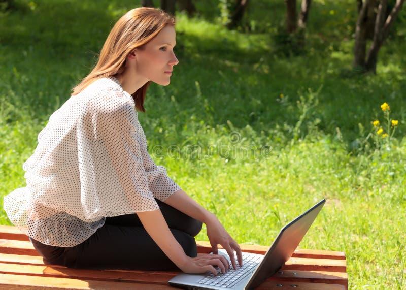 Jeune femme avec l'ordinateur portatif sur un banc photo stock