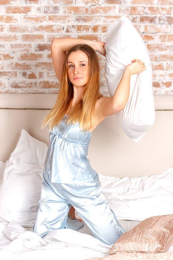 Jeune femme avec l'oreiller photo stock
