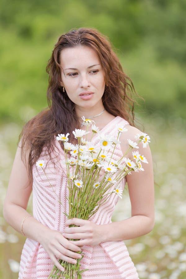 Jeune femme avec la camomille de bouquet posant sur le pré de la camomille photo stock