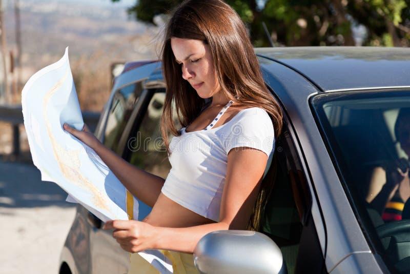 Jeune femme avec la carte près du véhicule photographie stock
