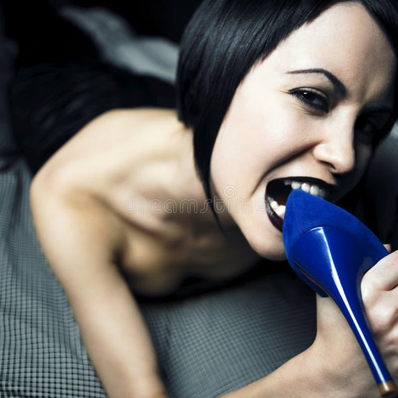 Jeune femme avec la chaussure dans une bouche photos libres de droits