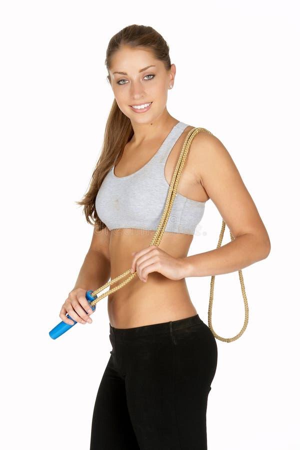 Jeune femme avec la corde de saut au-dessus de l'épaule photo stock