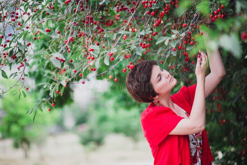 Jeune femme avec la coupe de cheveux courte tenant le cerisier proche photo stock