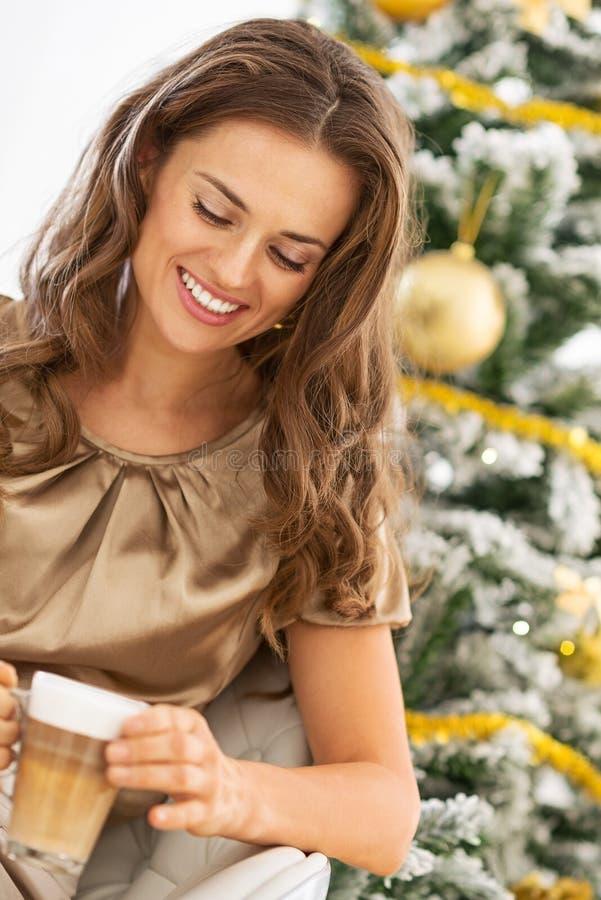 Jeune femme avec la crème de latte devant l'arbre de Noël images libres de droits