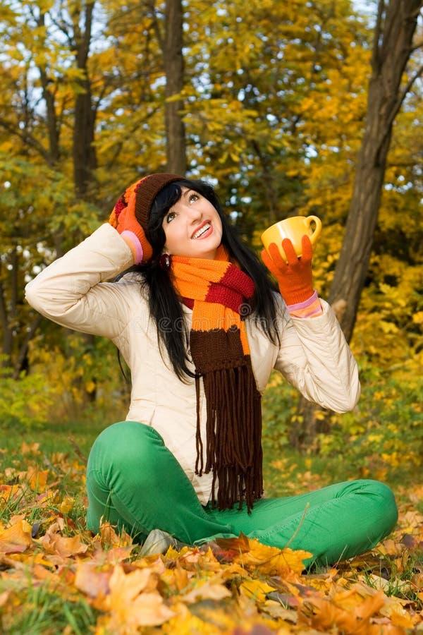 Jeune femme avec la cuvette de thé en stationnement d'automne photos stock