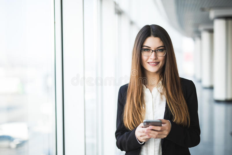 Jeune femme avec la dactylographie au téléphone portable dans le bureau photos libres de droits
