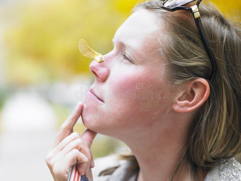 Jeune femme avec la graine d'érable sur le nez photographie stock libre de droits