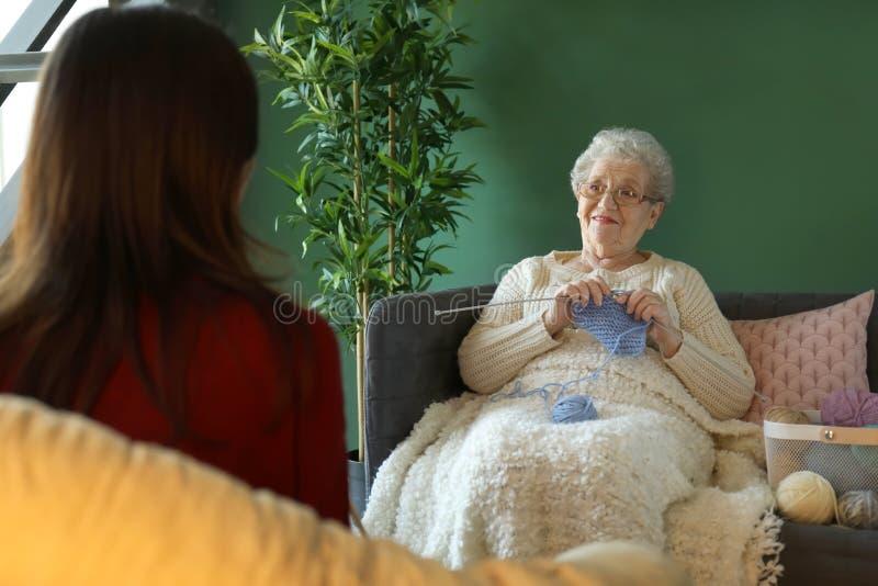 Jeune femme avec la grand-mère tricotant ensemble à la maison image libre de droits