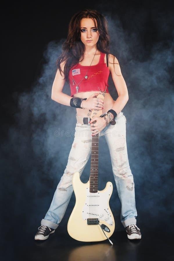 Jeune femme avec la guitare électrique dans la fumée image stock