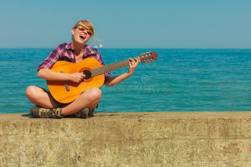 Jeune femme avec la guitare extérieure image stock