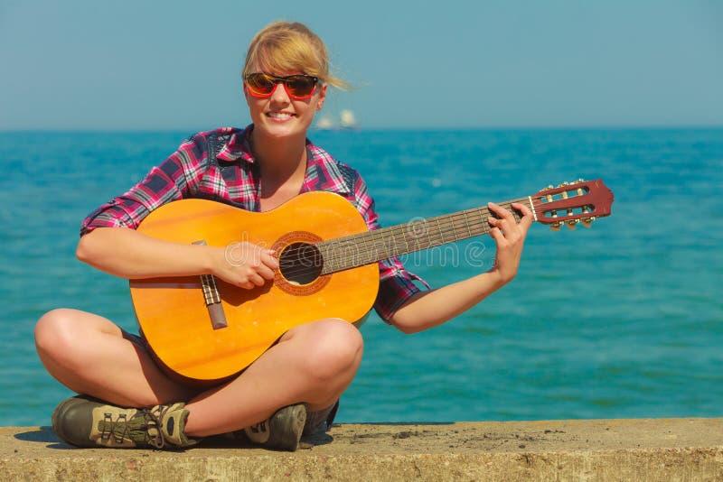 Jeune femme avec la guitare extérieure photo stock