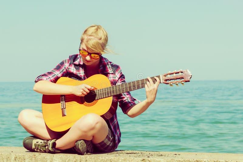 Jeune femme avec la guitare extérieure photos libres de droits