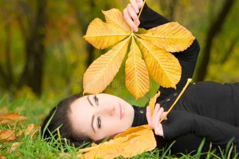 Jeune femme avec la lame d'automne photographie stock libre de droits