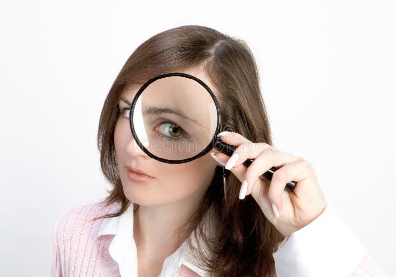 Jeune femme avec la loupe image stock