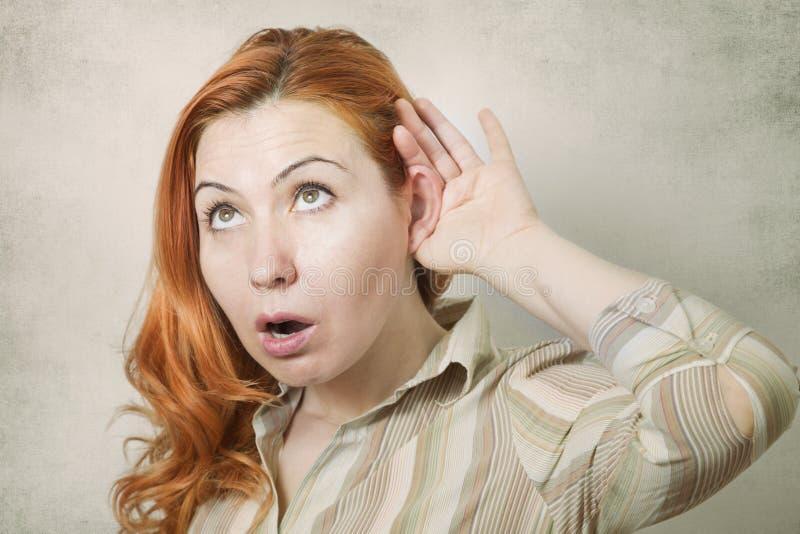 Jeune femme avec la main à l'écoute d'oreille photos stock