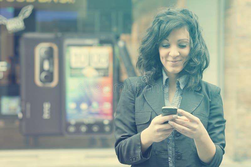 Jeune femme avec la marche de téléphone portable photos stock