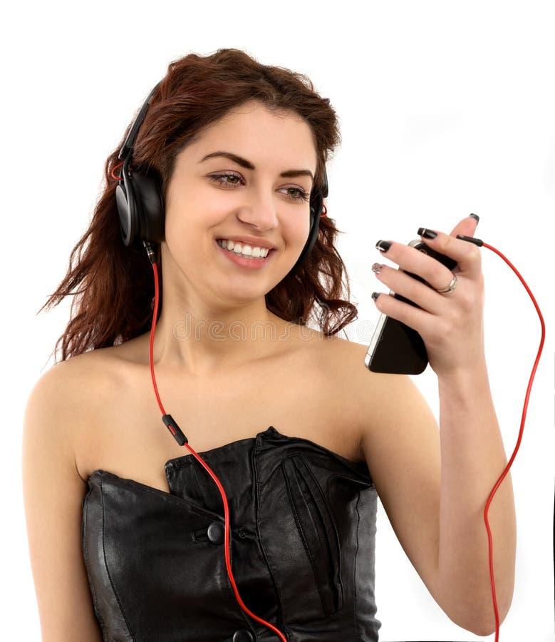 Jeune femme avec la musique de écoute d'écouteurs. Fille d'adolescent de musique photographie stock