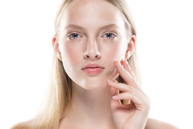 Jeune femme avec la peau de beauté visage émouvant de main d'isolement sur le whi photos stock
