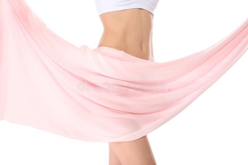 Jeune femme avec la peau lisse parfaite et tissu mou sur le fond blanc, plan rapproché de ventre images libres de droits