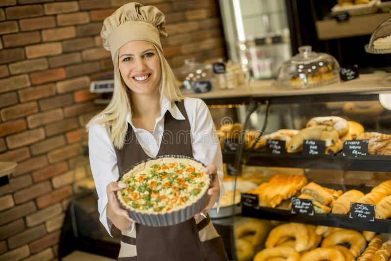 Jeune femme avec la quiche Lorraine dans la boulangerie image libre de droits