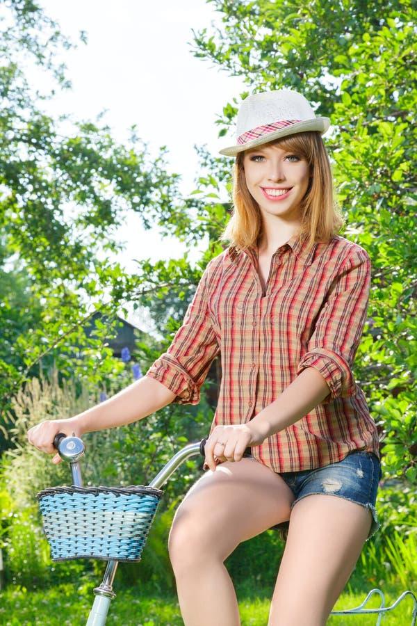 Jeune femme avec la rétro bicyclette photographie stock