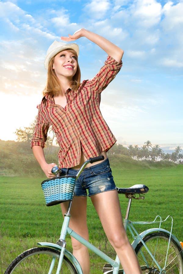 Jeune femme avec la rétro bicyclette en parc image libre de droits