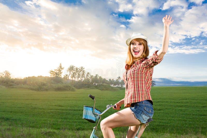 Jeune femme avec la rétro bicyclette en parc images stock