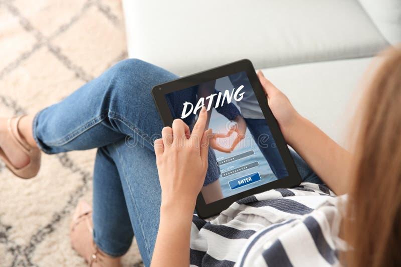 Jeune femme avec la tablette utilisant le site Web pour la datation en ligne à la maison photos stock